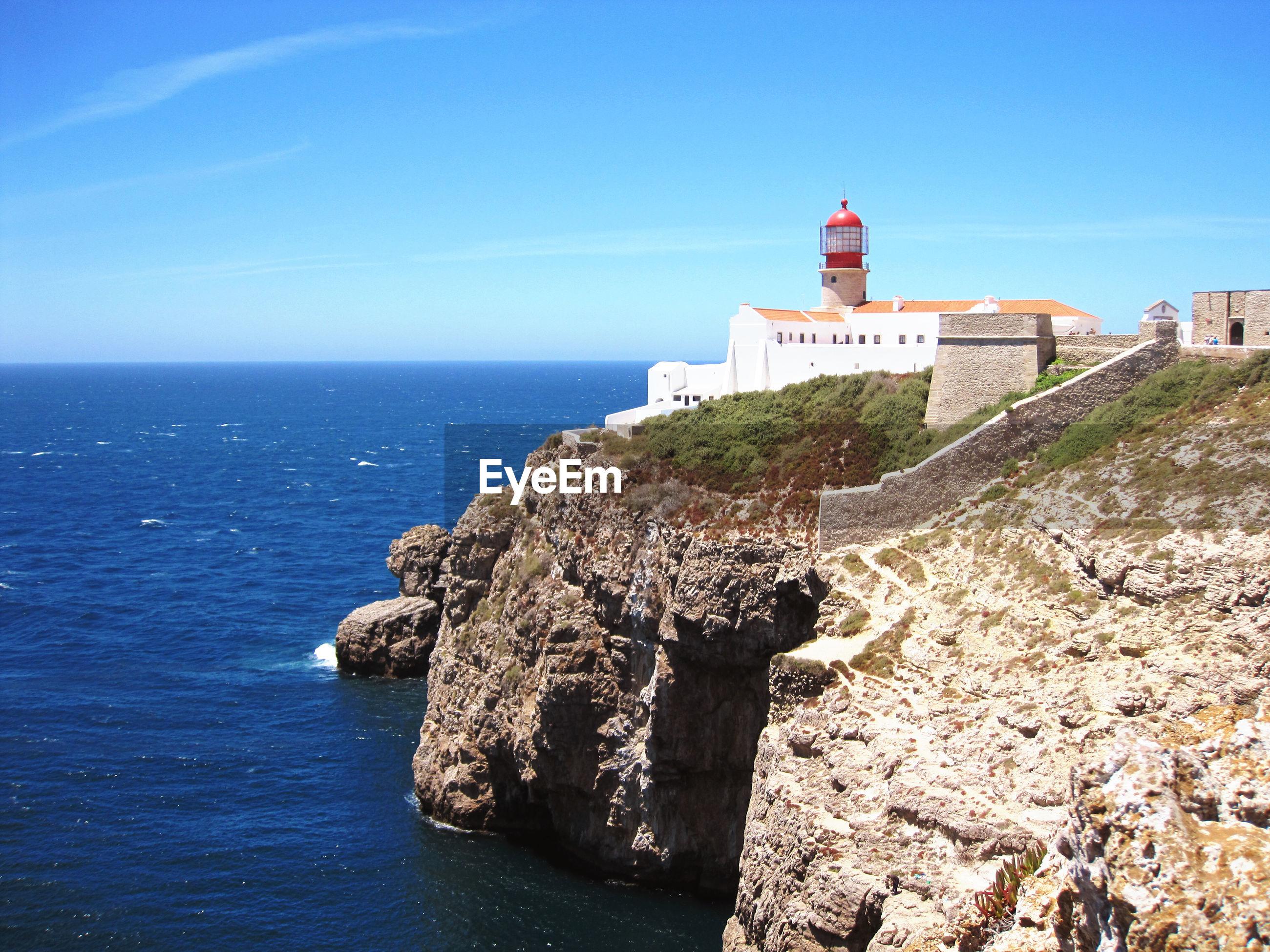 Lighthouse on building by sea against blue sky