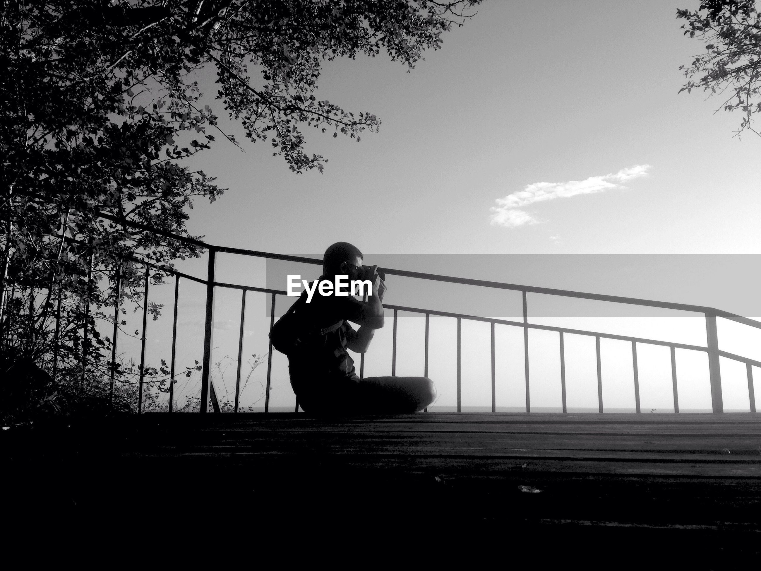 Man photographing while sitting on steps against sky