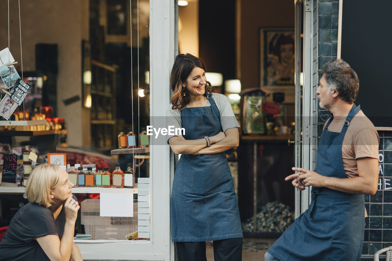 store, standing, real people, casual clothing, adult, two people, retail, young adult, men, smiling, communication, women, lifestyles, business, three quarter length, focus on foreground, people, young women, small business, entrepreneur, retail display