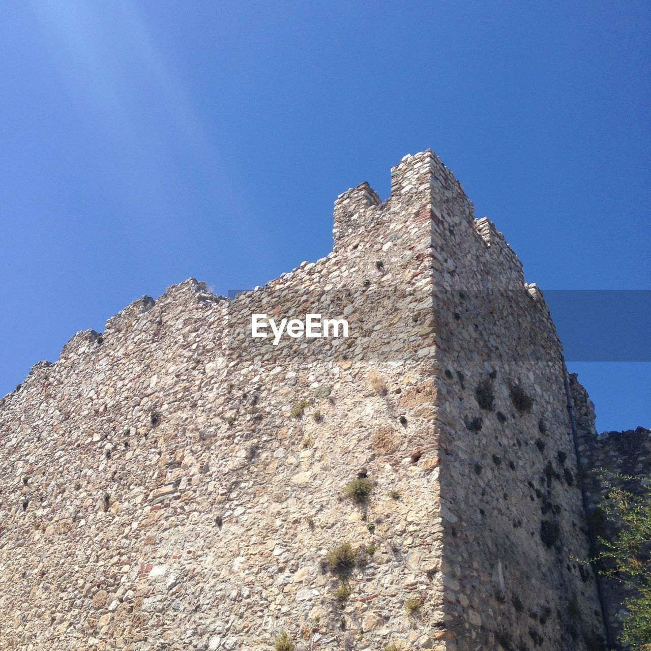 low angle view, clear sky, blue, history, day, no people, ancient, architecture, outdoors, sunlight, castle, old ruin, ancient civilization, built structure, mountain, nature, building exterior, sky