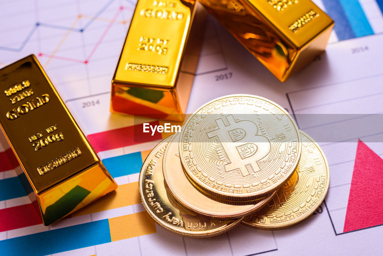 HIGH ANGLE VIEW OF COINS ON TABLE AND YELLOW METAL
