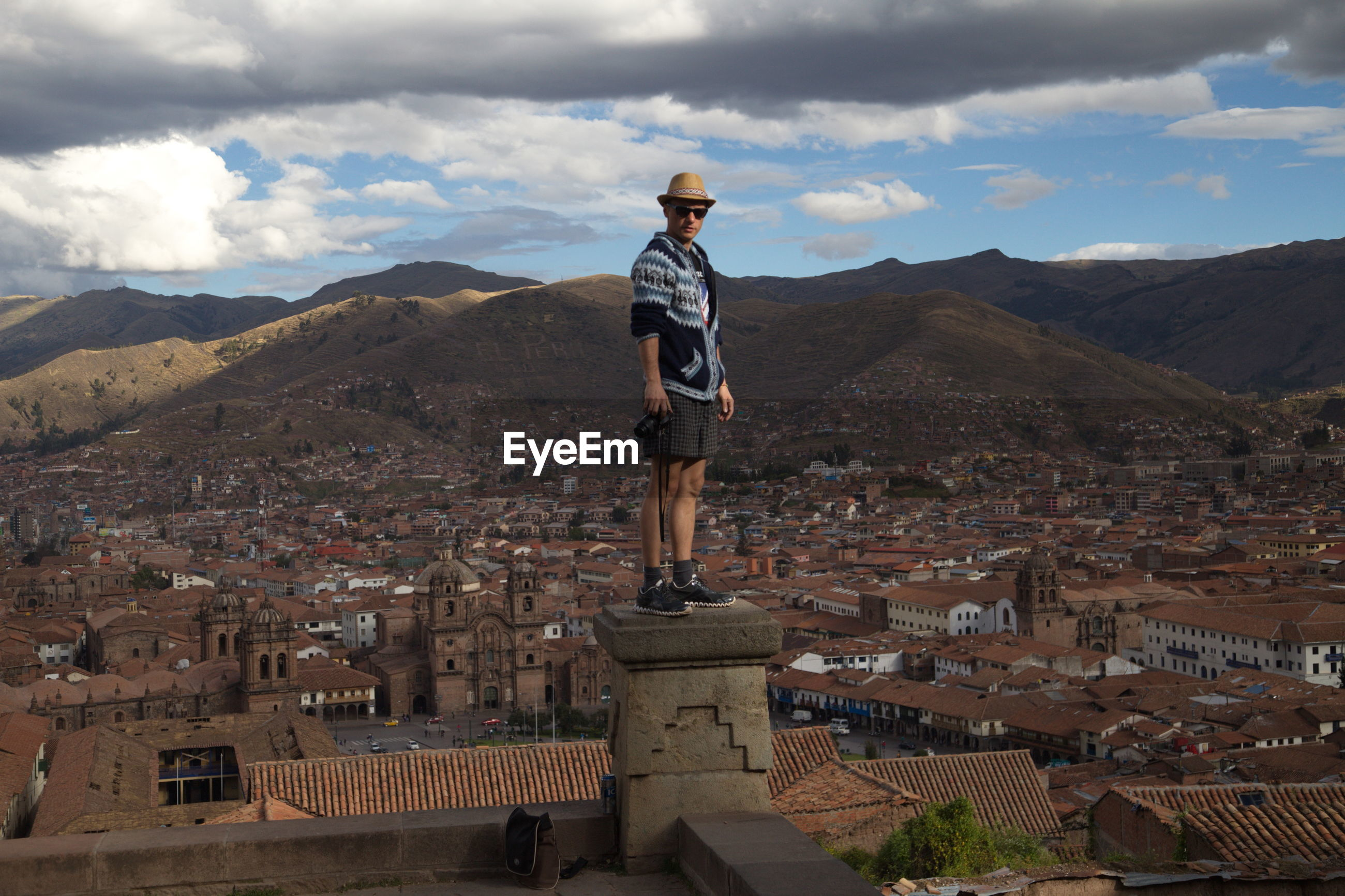 Man standing at observation point over cityscape against sky