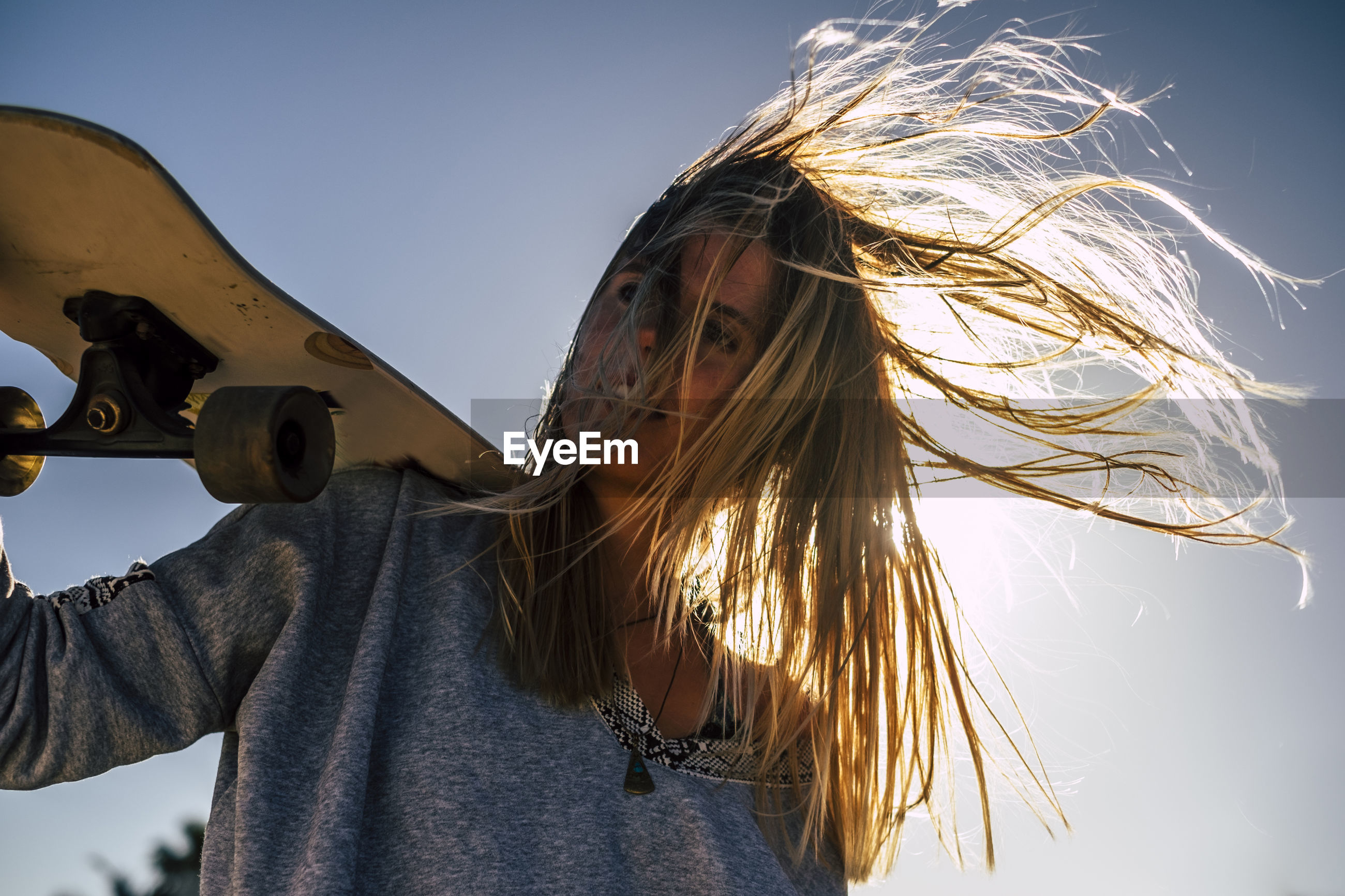 Portrait of smiling woman holding skateboard against sky