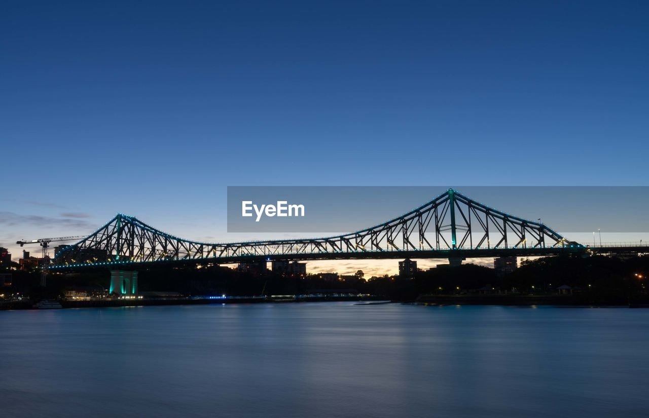sky, water, bridge, architecture, clear sky, connection, bridge - man made structure, waterfront, built structure, river, copy space, blue, nature, no people, transportation, illuminated, reflection, travel destinations, outdoors