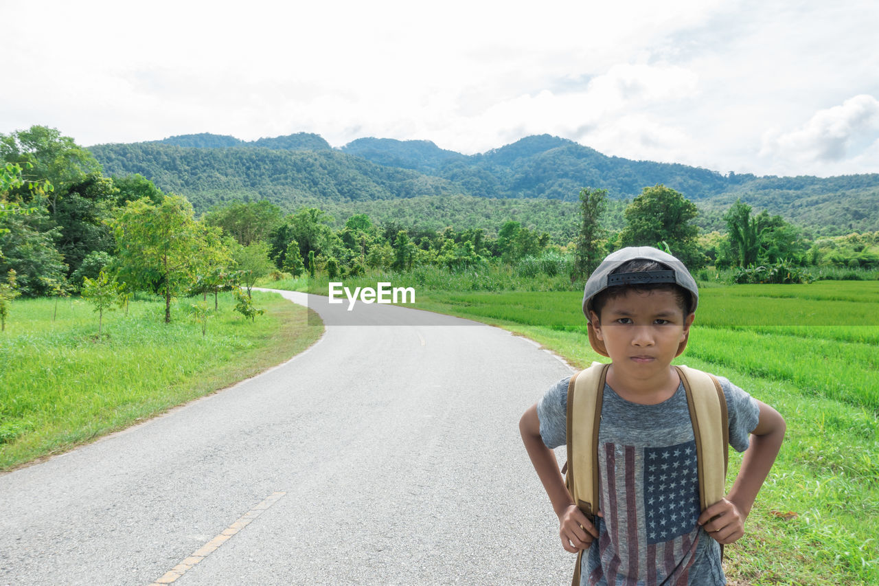 Portrait Of Boy Standing On Road Amidst Field Against Sky