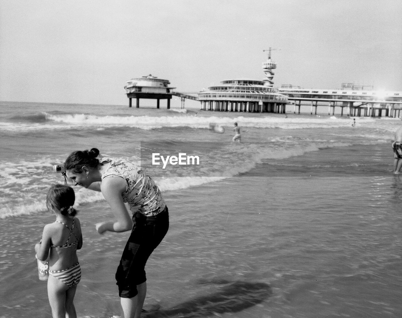 Mother and daughter in sea against sky