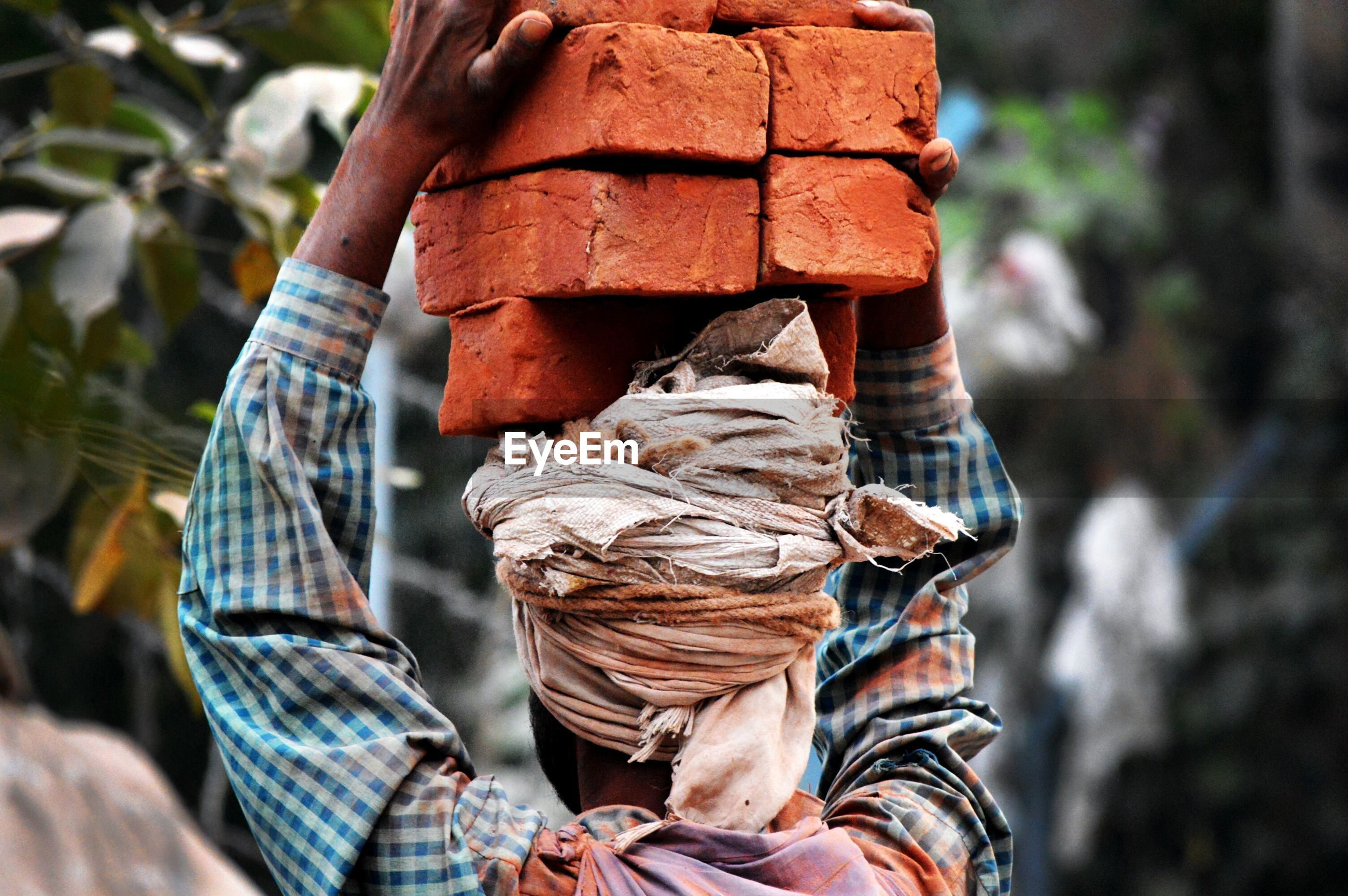 Rear view of worker carrying bricks at construction site