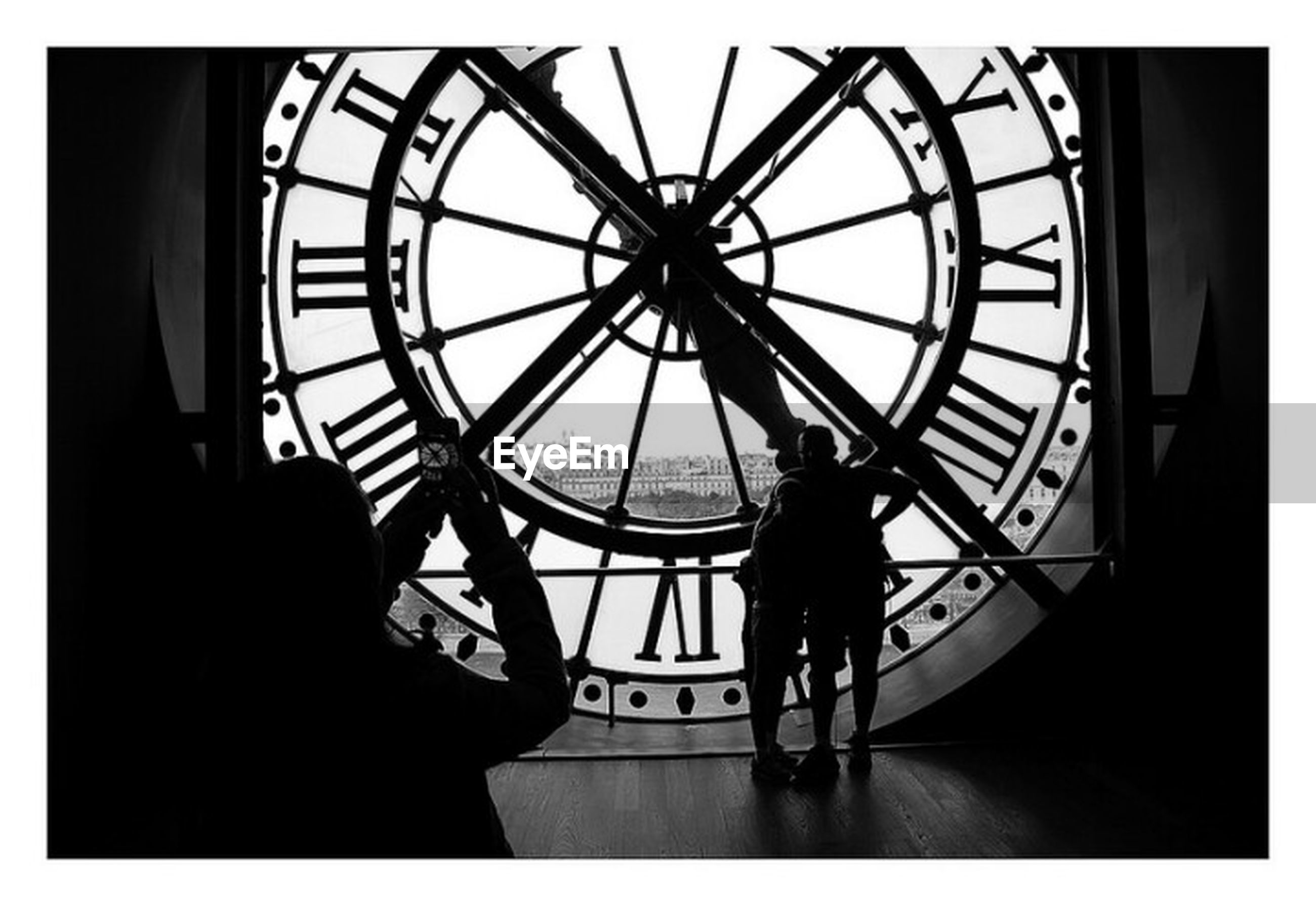 clock, time, roman numeral, silhouette, standing, real people, men, leisure activity, clock face, day, two people, clock tower, minute hand, indoors, teamwork, hour hand, adult, people
