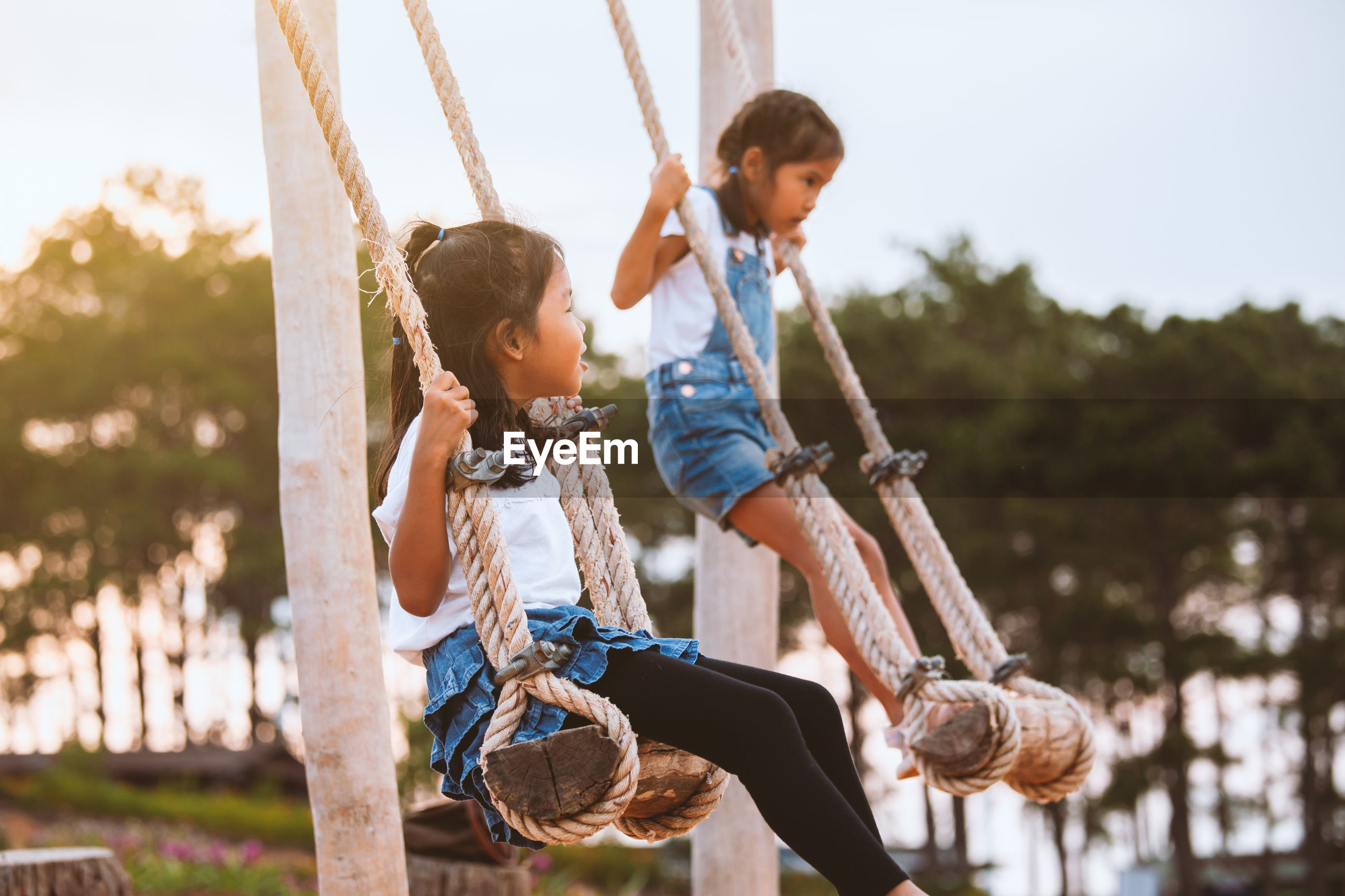 Sisters swinging at playground
