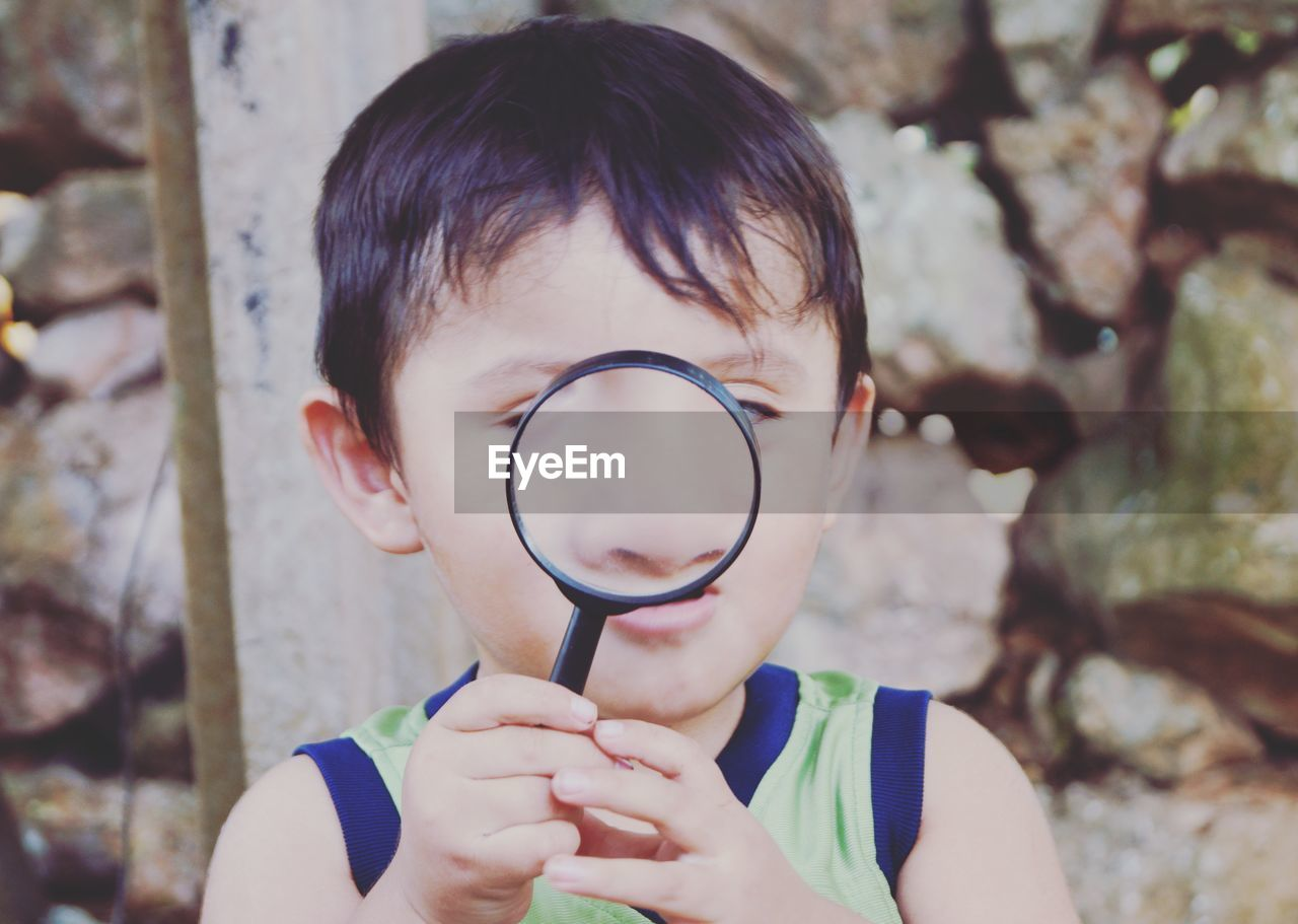 Close-up of boy playing with magnifying glass