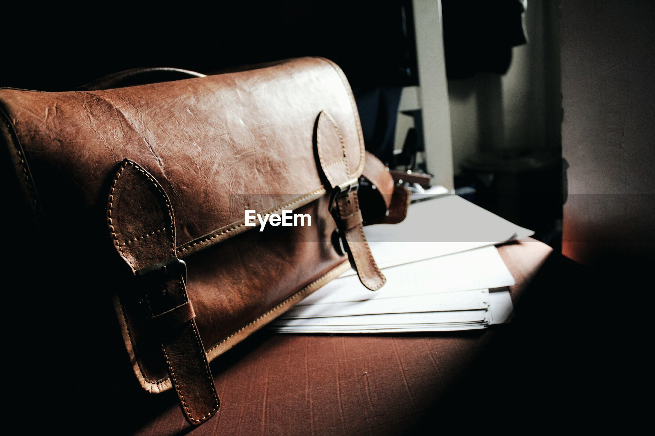 Close-up of leather bag with papers on wooden table