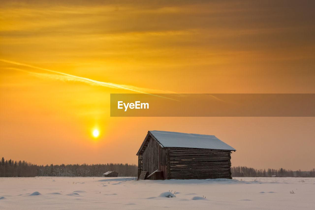 Old barn on landscape against sky during sunset