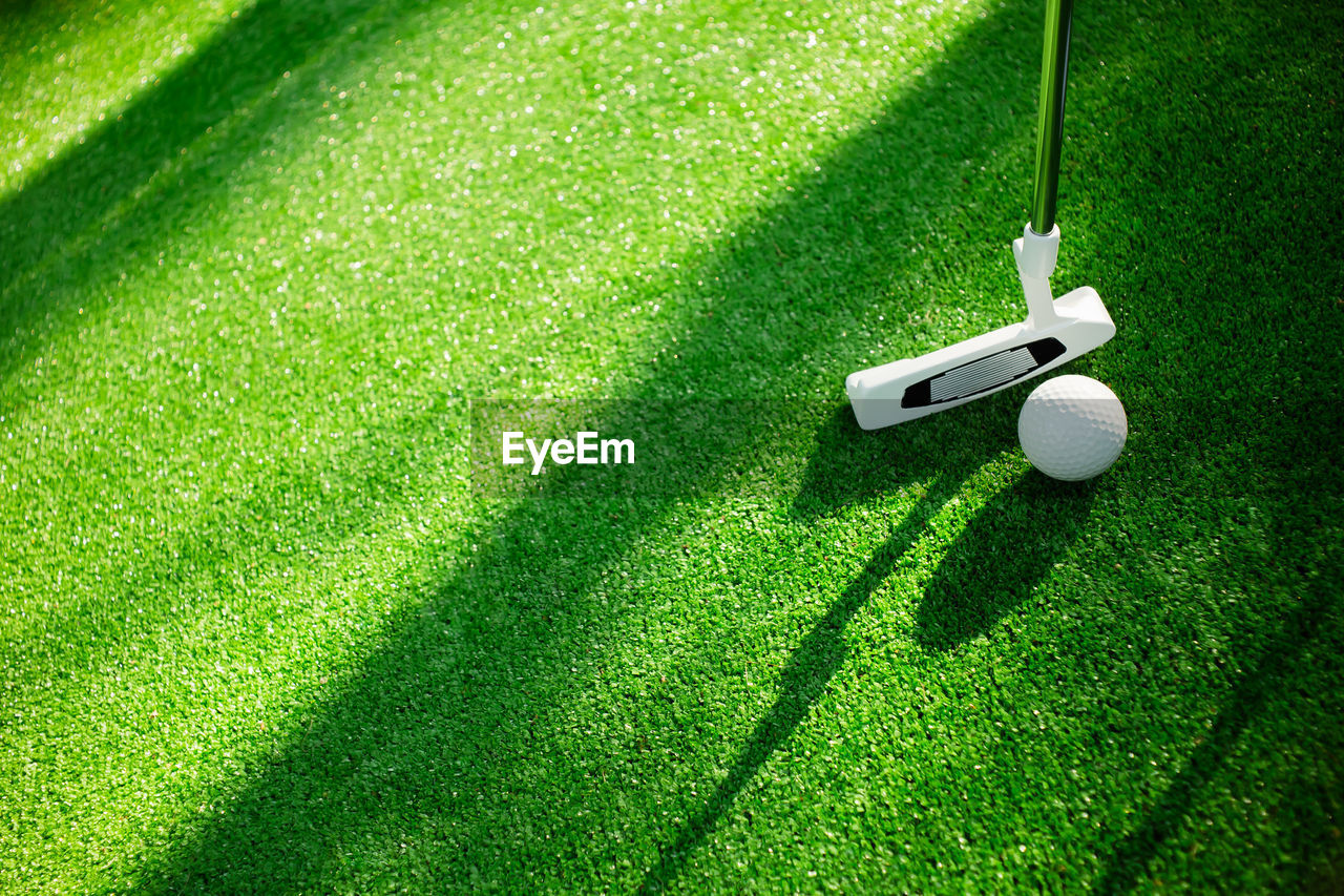 grass, green color, shadow, golf, plant, nature, ball, golf course, high angle view, sunlight, leisure activity, no people, green - golf course, golf ball, sport, activity, day, outdoors, lawn, equipment, turf