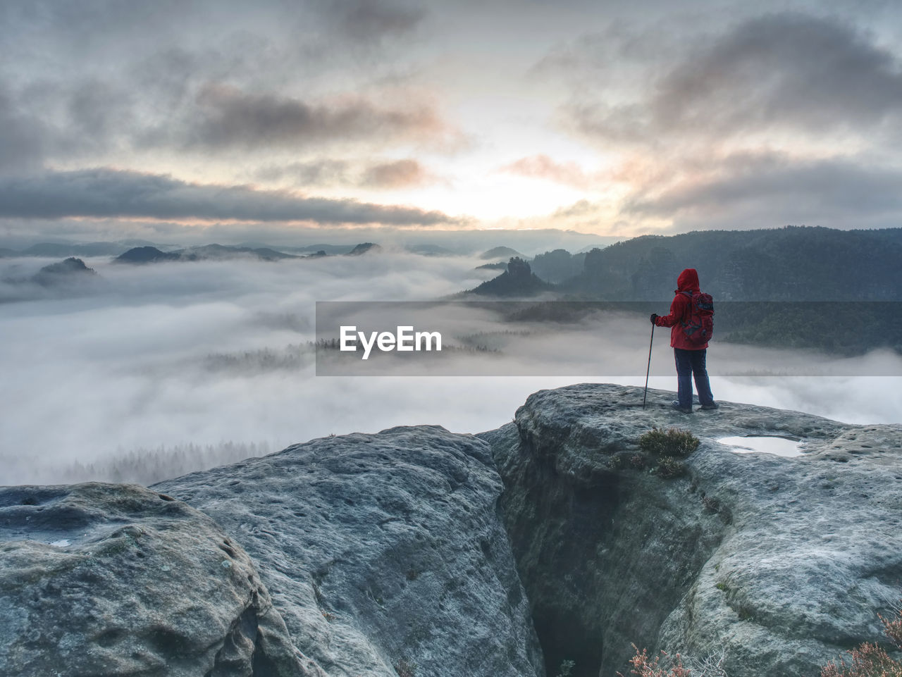 Alone woman hiker in rocks while extreme misty weather. autumn hike in rocks for hard adventurer
