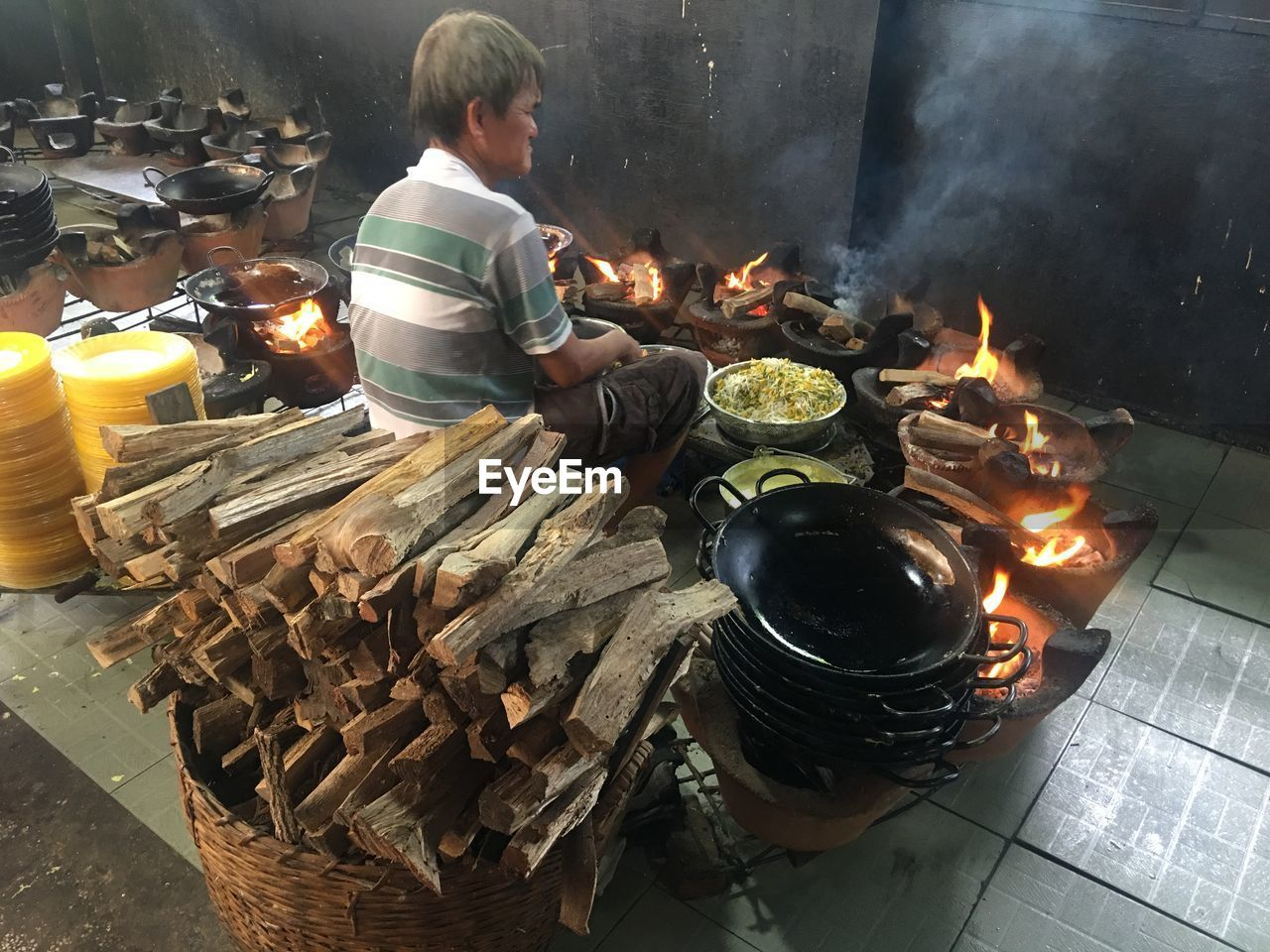 burning, heat - temperature, fire, real people, fire - natural phenomenon, flame, food, food and drink, one person, preparation, men, preparing food, nature, firewood, smoke - physical structure, wood - material, glowing, log, kitchen utensil