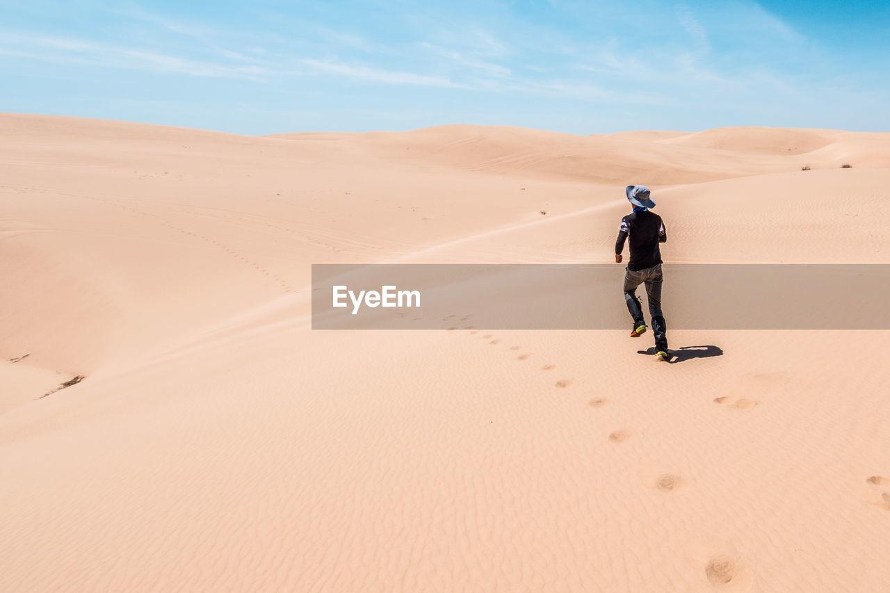 Man Running In Desert Against Sky