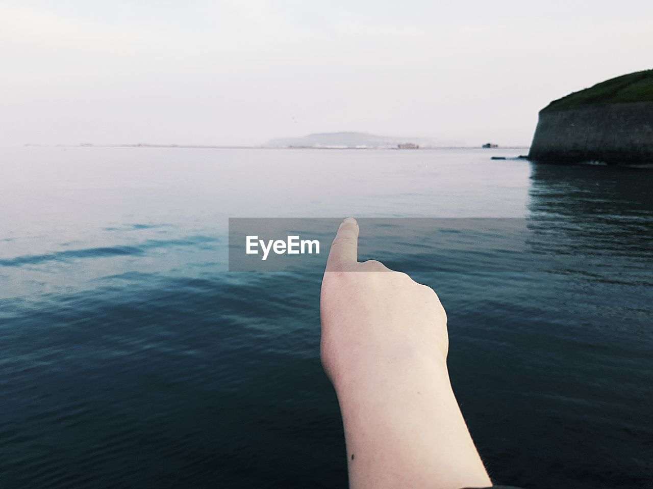 Rear View Of Person Pointing Finger Towards Sea