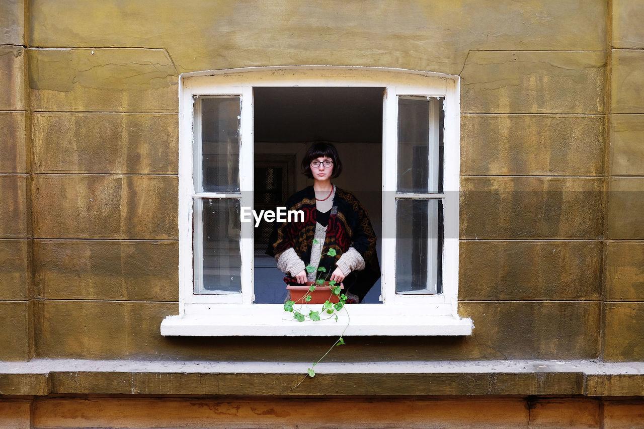 Portrait of woman standing in window