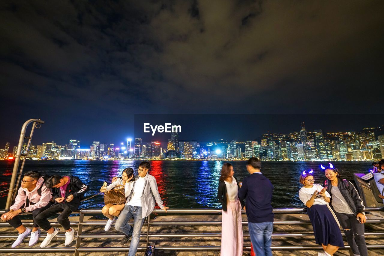 architecture, building exterior, built structure, water, sky, night, city, illuminated, men, group of people, cityscape, nature, real people, building, cloud - sky, women, leisure activity, adult, office building exterior, skyscraper, outdoors