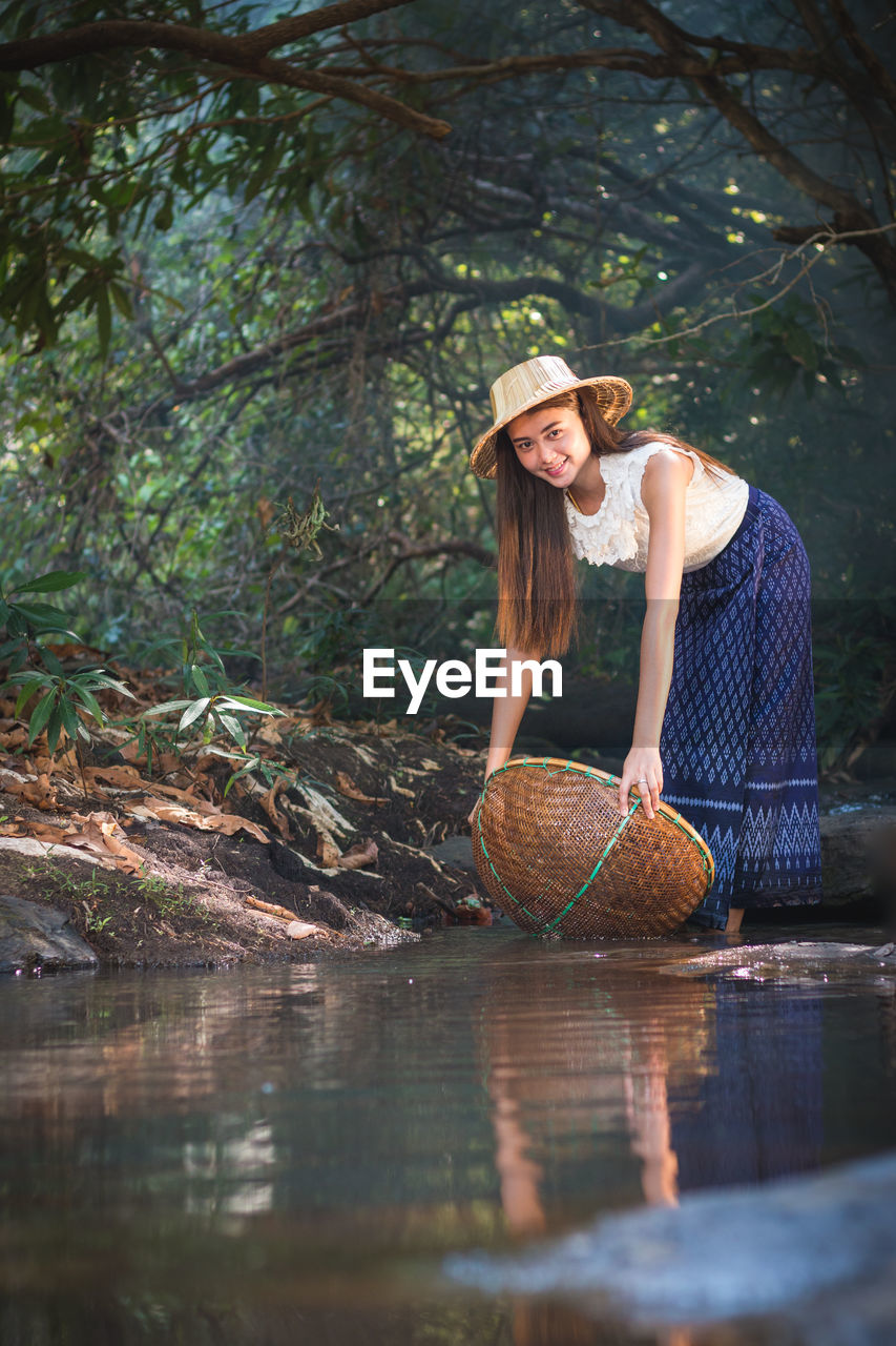 one person, hat, young adult, front view, basket, portrait, real people, looking at camera, plant, young women, adult, clothing, water, tree, leisure activity, women, nature, casual clothing, outdoors, hairstyle