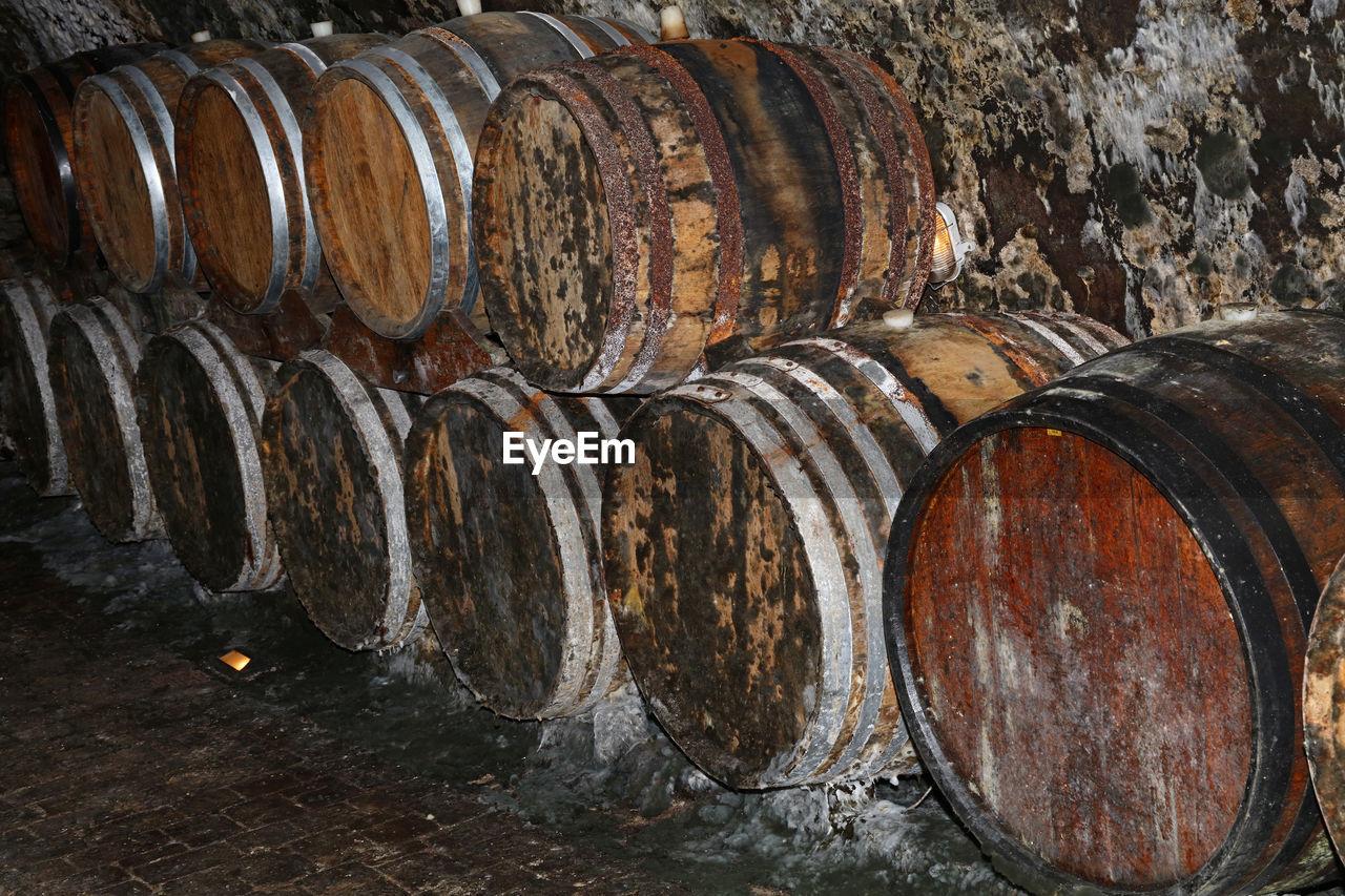 Stack Of Old Barrels In Wine Cellar