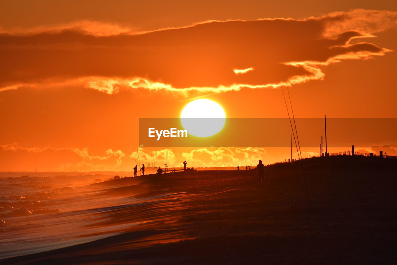 Scenic view of silhouette beach against sky during sunset
