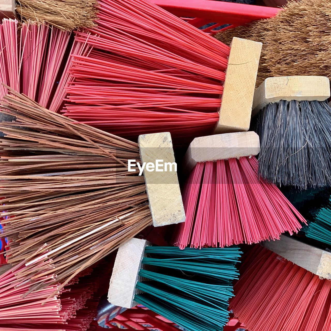 large group of objects, choice, variation, multi colored, abundance, broom, no people, red, still life, full frame, high angle view, cleaning, indoors, backgrounds, close-up, wood - material, cleaning equipment, brush, heap, retail
