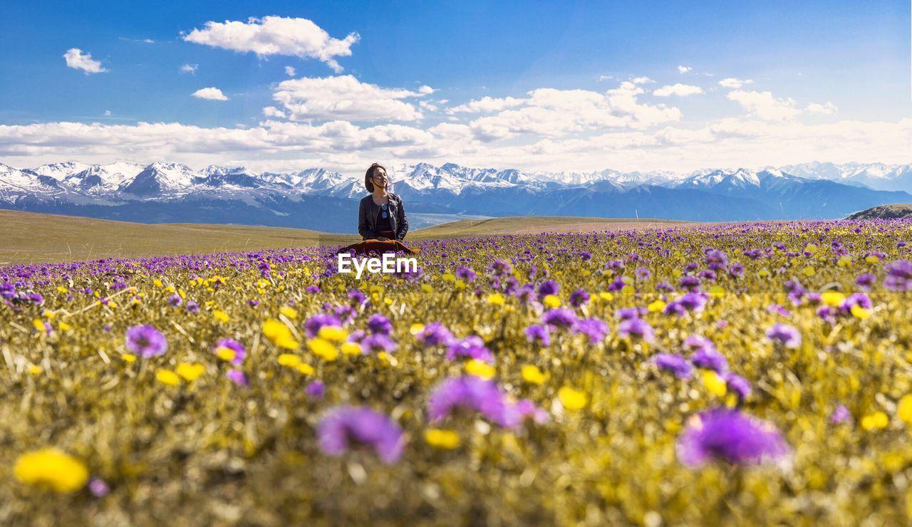 WOMAN SITTING ON FIELD OF FLOWERING PLANTS