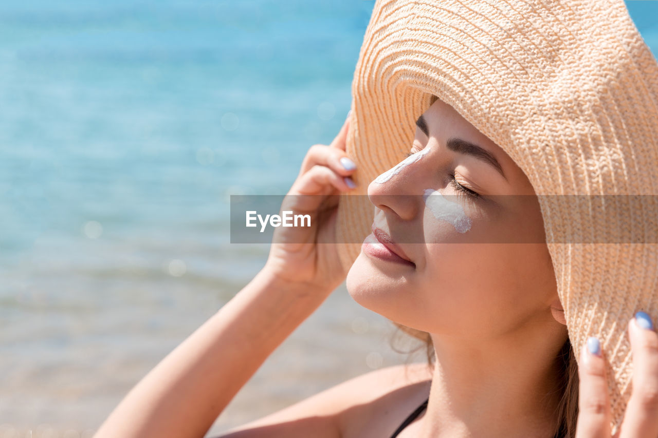 one person, water, hat, headshot, leisure activity, lifestyles, close-up, clothing, portrait, women, beach, young adult, real people, human body part, sea, nature, young women, land, body part, sun hat, outdoors, beautiful woman, human face