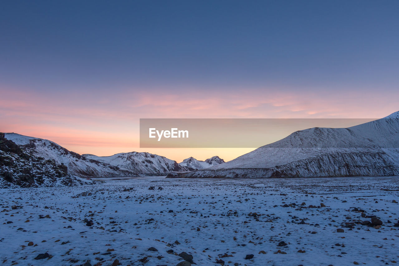 SCENIC VIEW OF SNOW COVERED MOUNTAINS AGAINST SKY AT SUNSET