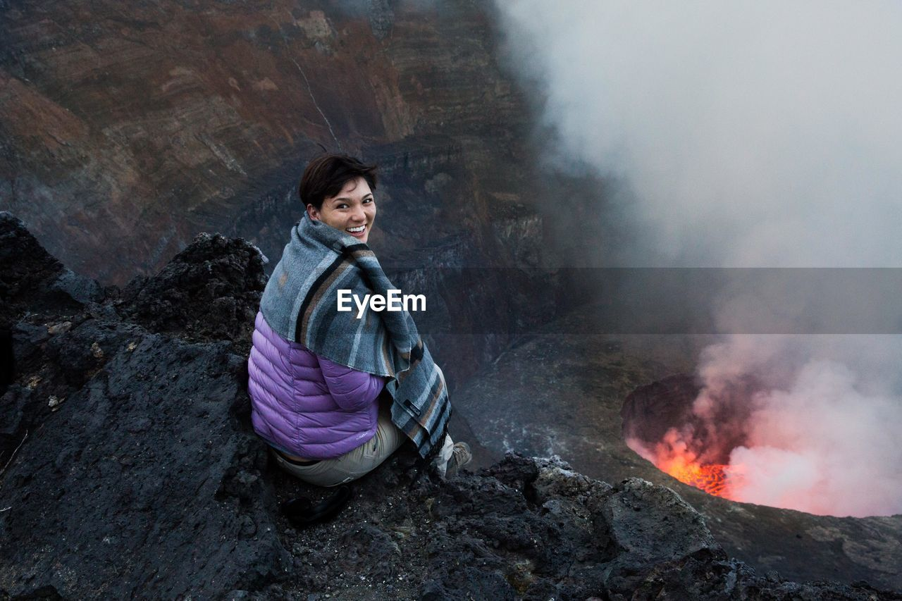 Woman Looking At Erupting Volcano