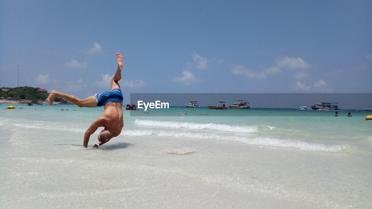 Shirtless man jumping at beach against sky