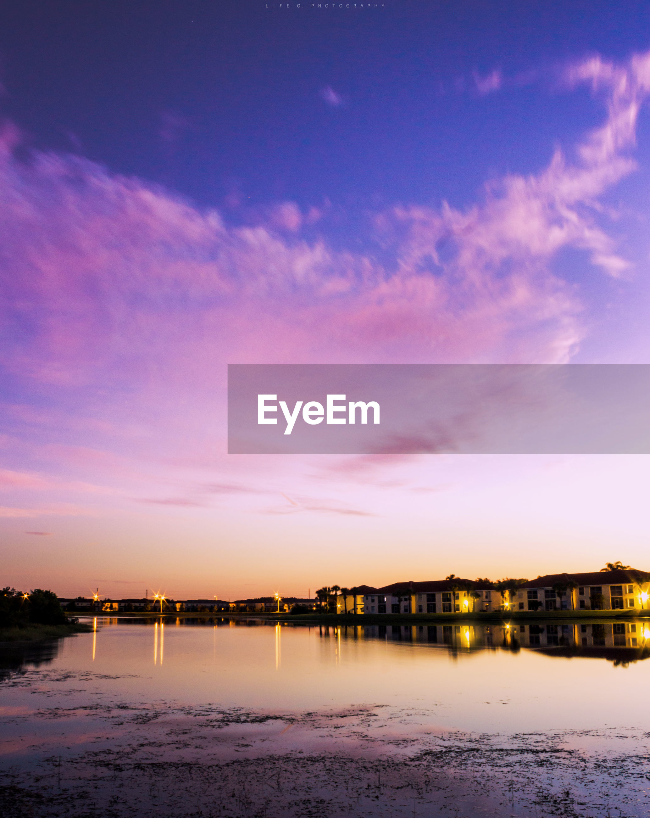 Houses by river with sky in background