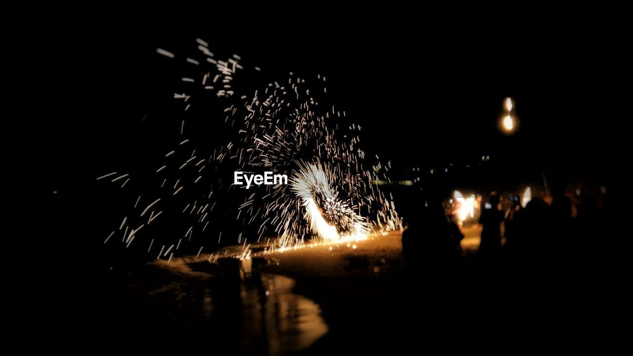 night, long exposure, firework display, firework - man made object, sparks, illuminated, motion, celebration, glowing, blurred motion, exploding, arts culture and entertainment, firework, sparkler, event, burning, celebration event, outdoors, water, sky, real people, wire wool