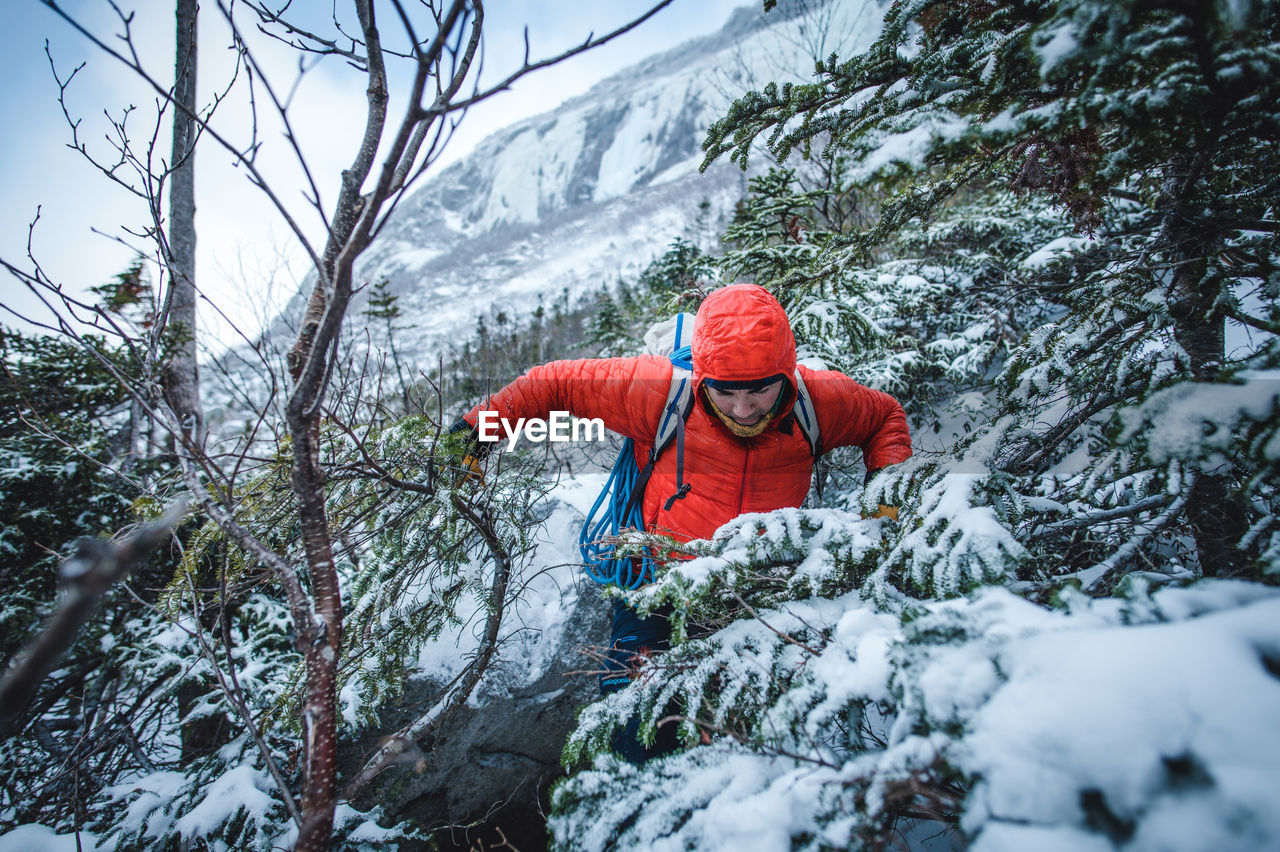 MIDSECTION OF PERSON ON SNOW COVERED LAND