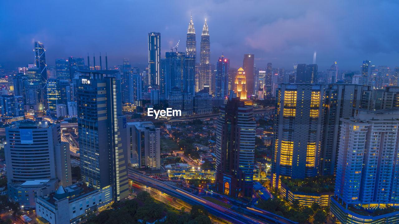 ILLUMINATED BUILDINGS AGAINST SKY IN CITY