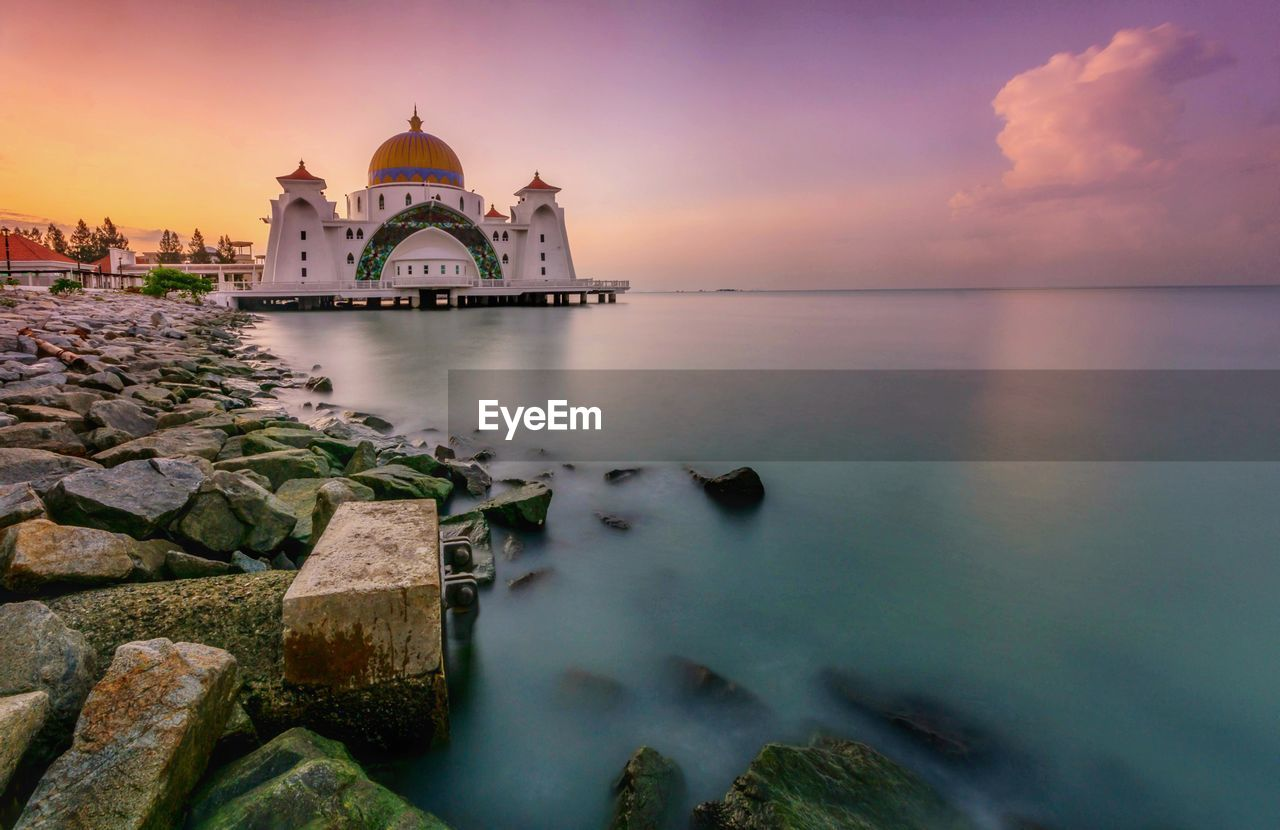 architecture, built structure, spirituality, religion, dome, sunset, building exterior, water, place of worship, sky, travel destinations, history, cloud - sky, outdoors, nature, no people, sea, day