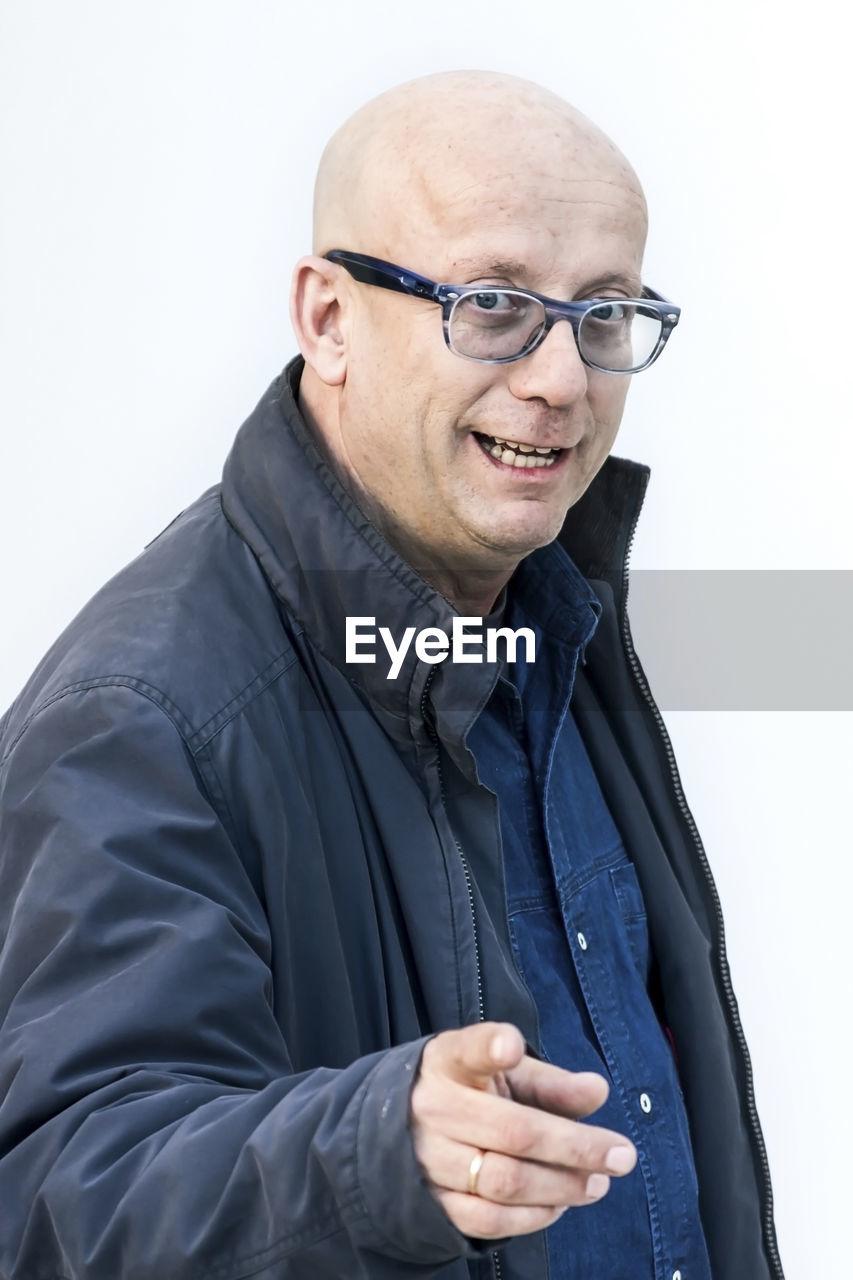 Portrait of smiling man wearing eyeglasses gesturing over white background