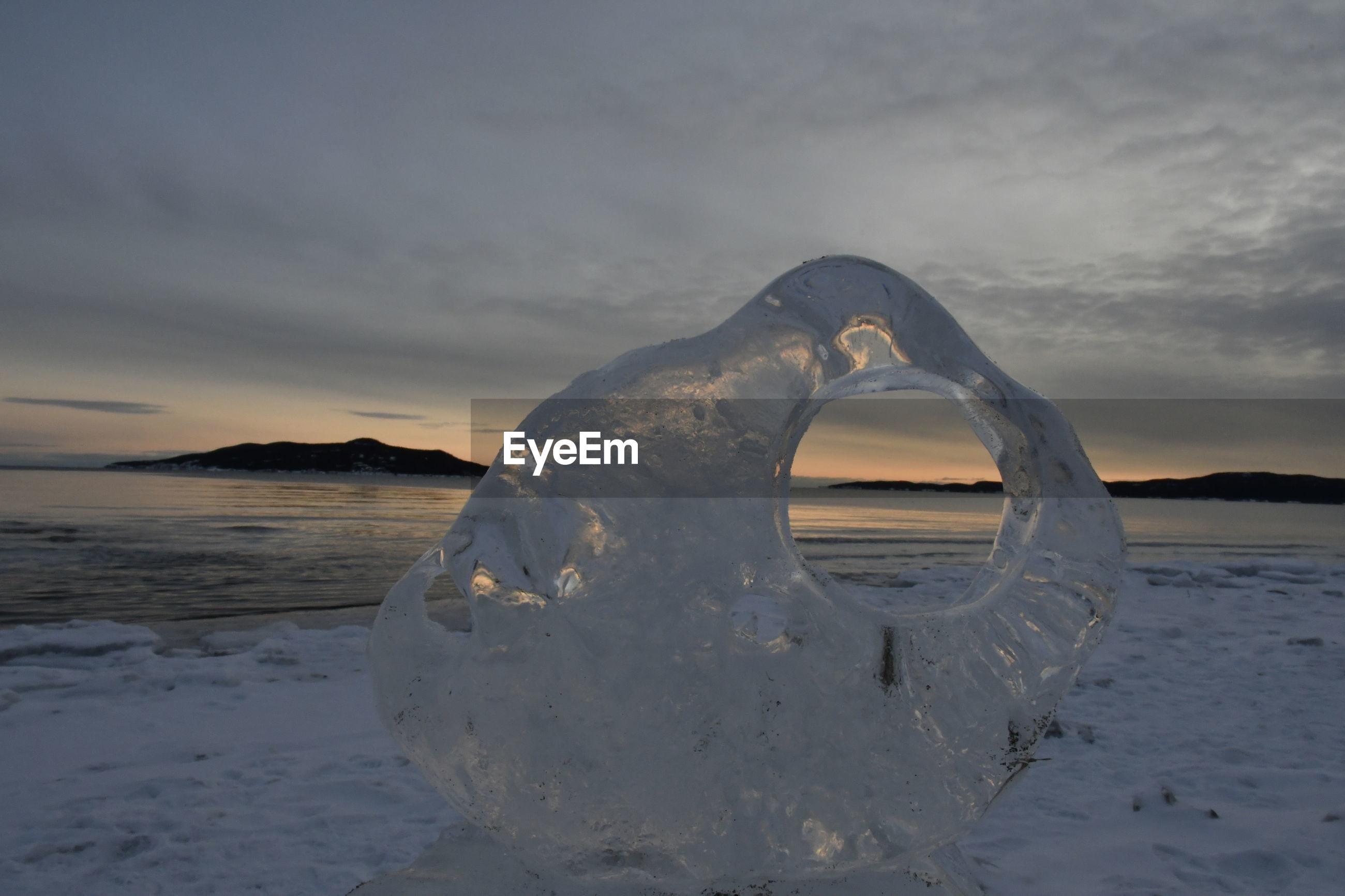 Frozen sea shore against sky during sunset