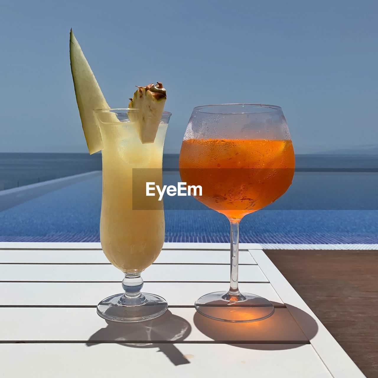 CLOSE-UP OF DRINK ON TABLE AGAINST SEA AND SKY