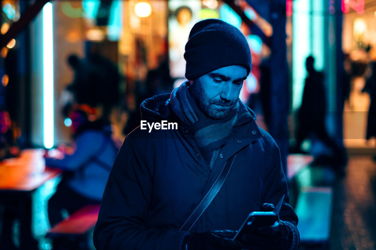 Portrait of young man with phone standing against illuminated city at night