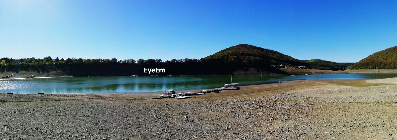 water, sky, scenics - nature, clear sky, tranquility, tranquil scene, beauty in nature, copy space, day, nature, lake, blue, beach, no people, tree, plant, non-urban scene, mountain, idyllic, outdoors
