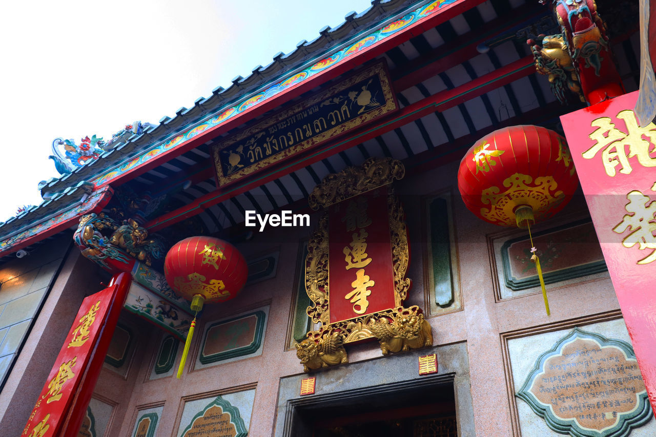 built structure, architecture, building exterior, low angle view, building, lantern, lighting equipment, belief, no people, place of worship, religion, spirituality, communication, decoration, text, non-western script, chinese lantern, outdoors, ornate