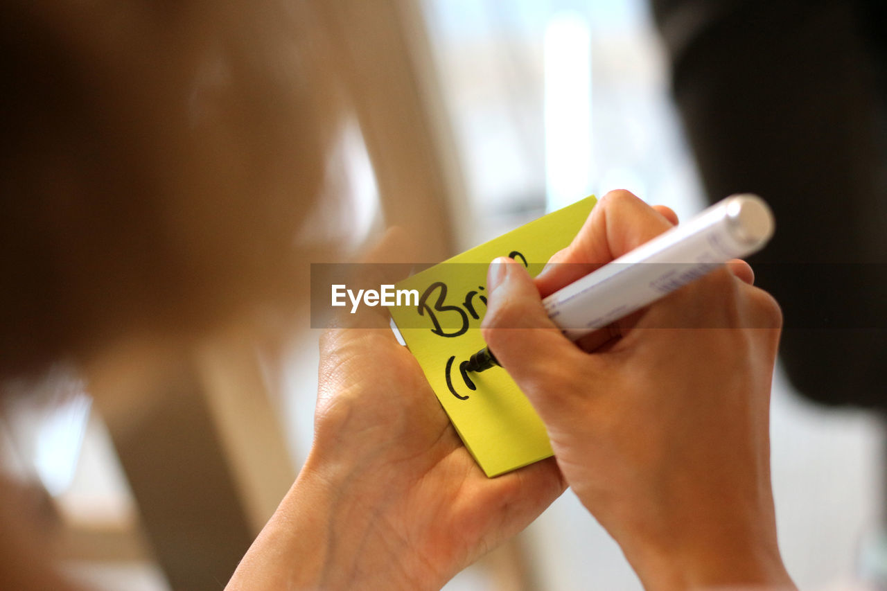 Cropped image of woman writing on adhesive note