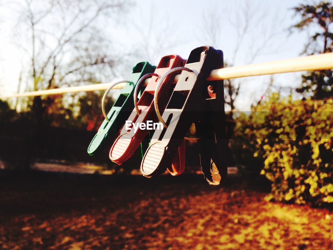 Close-Up Of Clothespins Hanging On Clothesline Against Sky
