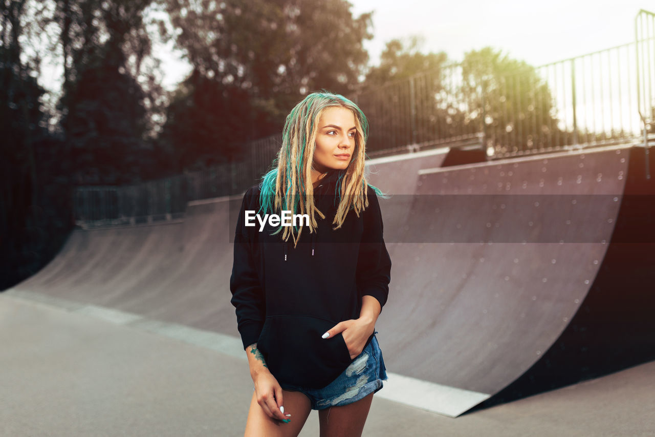 Beautiful Young Woman Standing At Skateboard Park