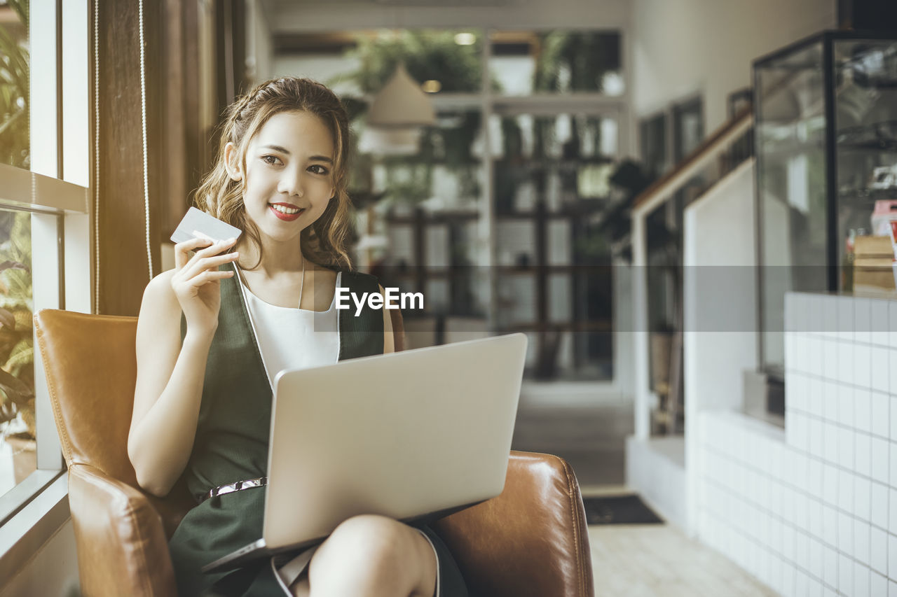 Young woman using laptop while sitting on armchair in cafe