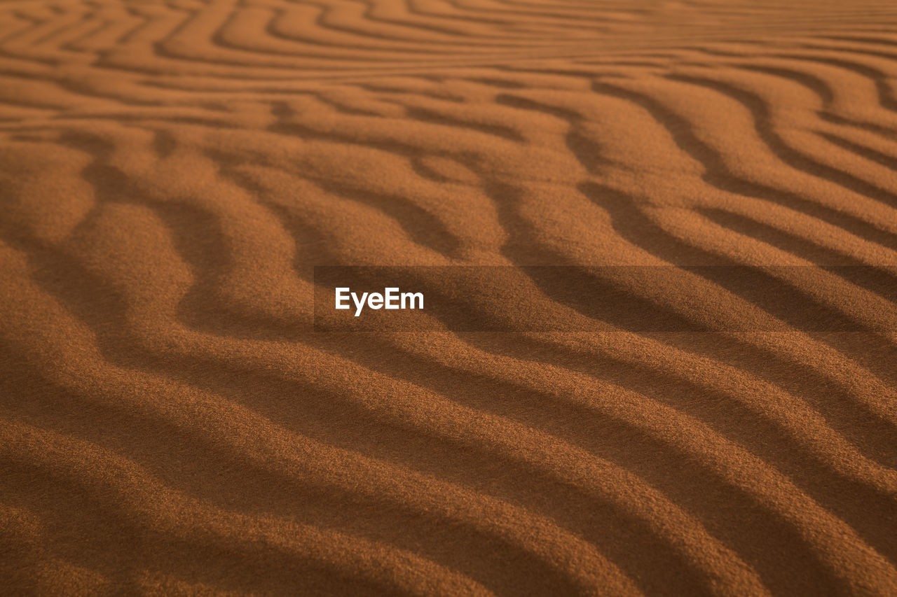 land, pattern, sand, landscape, desert, no people, wave pattern, high angle view, full frame, backgrounds, sand dune, scenics - nature, environment, tranquility, climate, nature, natural pattern, arid climate, brown, beauty in nature, atmospheric