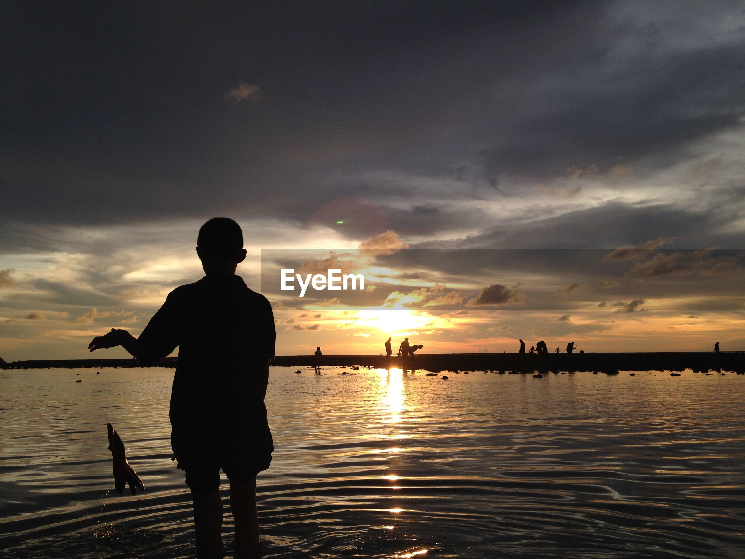 Silhouette boy standing in sea against sky during sunset