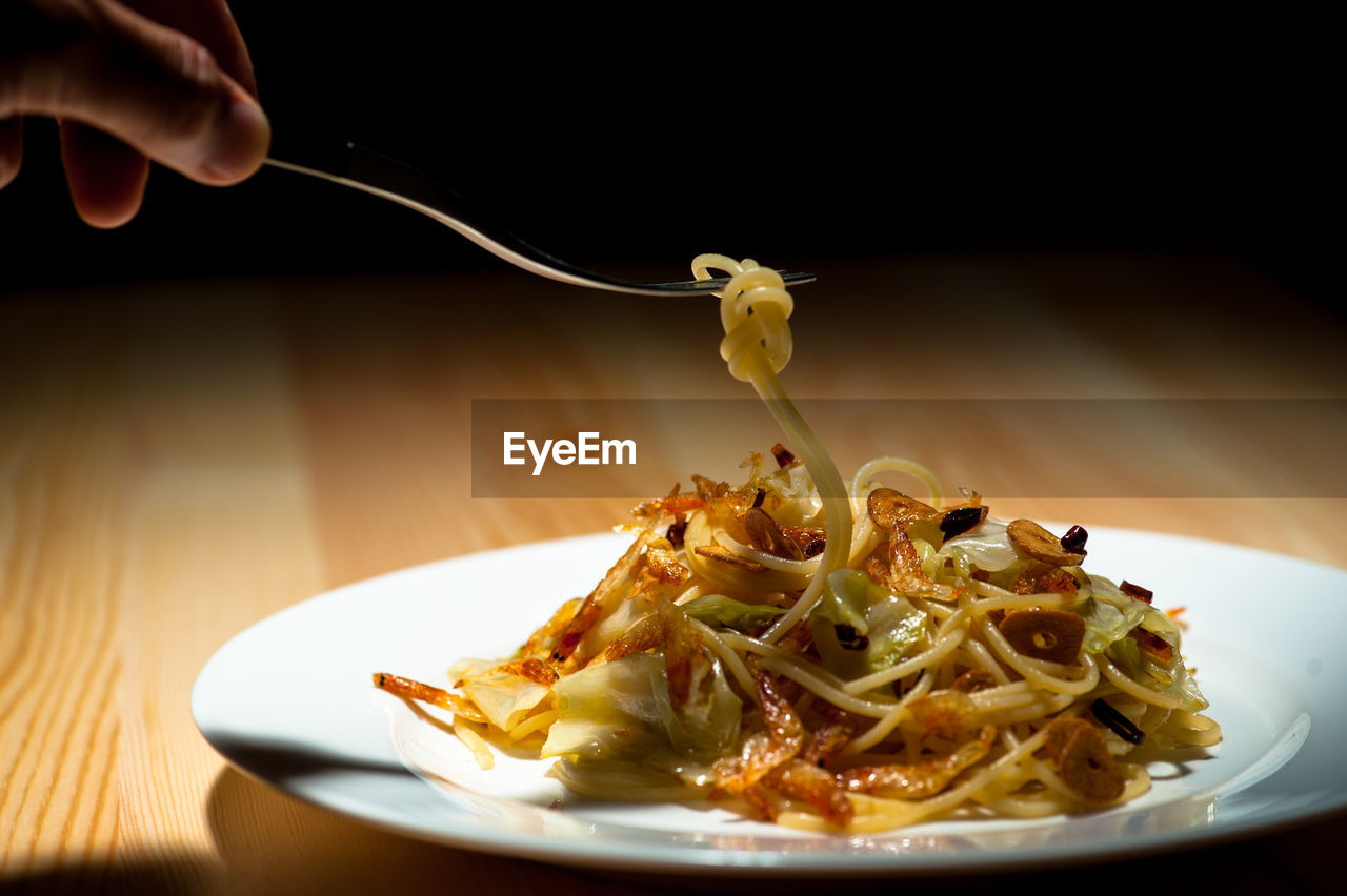 Cropped Image Of Hand Holding Noodles In Plate On Table